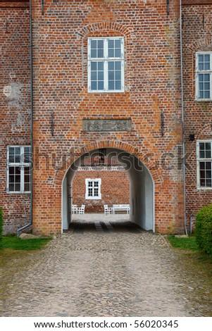 Entrance through an archway into a castle - stock photo