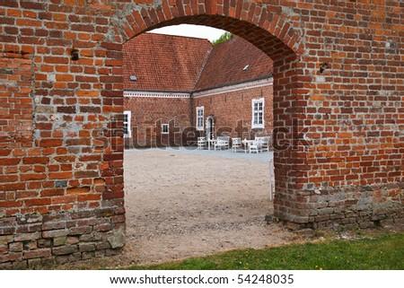 Entrance through an archway into a courtyard - stock photo