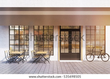 Entrance To A Cafe With Large Windows Wooden Tables Chairs And Bycicle Near