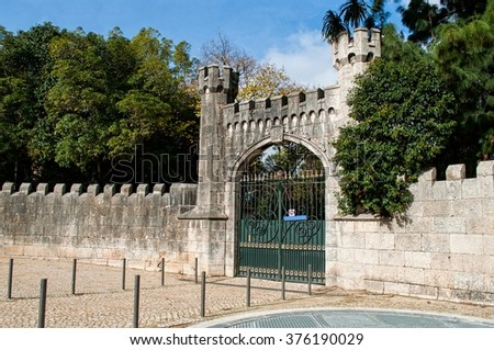 Entrance to a garden decorated with an ancient gate and an arched door - stock photo