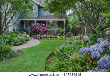 Entrance to a home through a beautiful garden, highlighted by rose and blue hydrangeas. - stock photo
