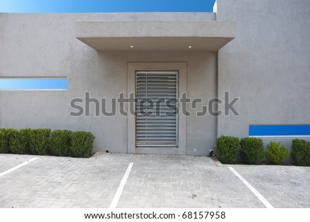 Entrance to a modern office, with parking in the foreground, and the sky shining through the windows and overhead - stock photo