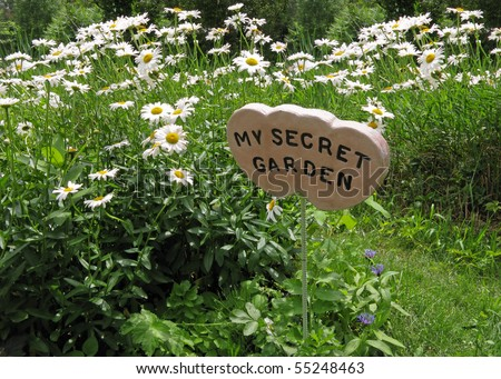 entrance to a secret garden surrounded by daisies - stock photo