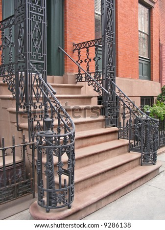 Entrance to Greenwich Village, NYC townhouse with ornate wrought iron railings - stock photo
