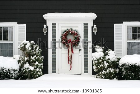 entrance to home with holiday wreath and snow - stock photo