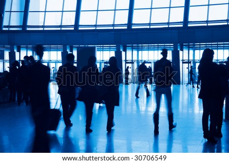 Entrance to modern building and people silhouettes.  Tint blue