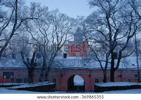 Entrance to Suomenlinna fortress island via main gate through arch in imperial Russian era historical jetty barracks and the clock tower on cold and foggy January winter morning in Helsinki, Finland. - stock photo