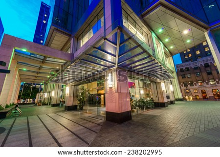 Entrance to the building lobby. Night scene of modern colorful city life with skyscrapers, highrise buildings. Vancouver downtown  at night. - stock photo