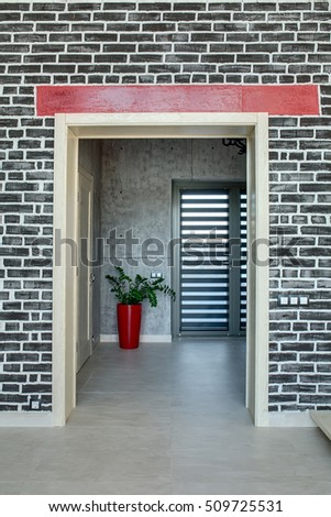 Entrance to the corridor in a modern style with brick and concrete walls. There are doors and a plant in the red pot. On the floor there are light tiles. Vertical.
