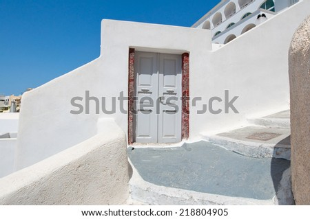 Entrance to the house carved into the rock on the edge of the caldera cliff in Fira town. Thira (Santorini), Greece. - stock photo