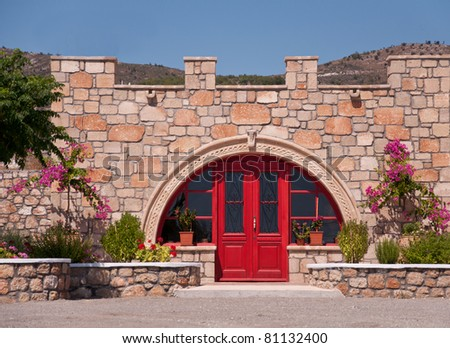 Entrance to the house decorated with flowers and yard with trees - typical in Greece - stock photo