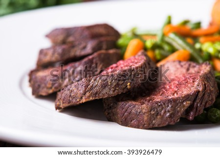 Entrecote with vegetables (carrots, green beans and peas) close up. - stock photo
