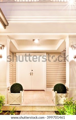 Entrence door of beautiful house with the two plant pot on each side in the night - stock photo