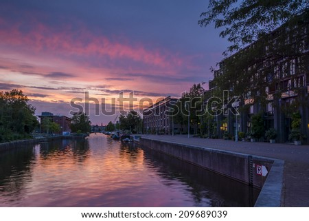 Entrepotdok canal, Amsterdam 2. Shortly after the sun had set on Nieuwevaart canal, I moved to another location nearby- a more sheltered waterway where the reflections were beautiful. - stock photo