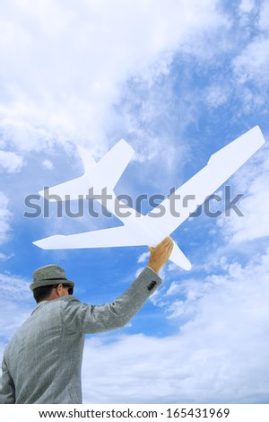 Entrepreneur businessman holds white model airplane flying in blue sky