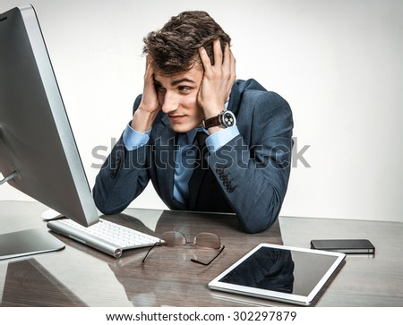 Entrepreneur dissatisfied with his earnings, profit, income, gain, benefit, margin / modern businessman at the workplace working with computer, depression and crisis concept - stock photo