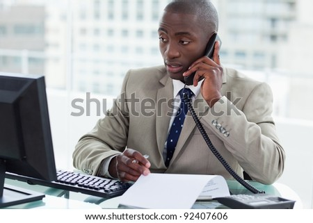Entrepreneur making a phone call while looking at his computer in his office - stock photo