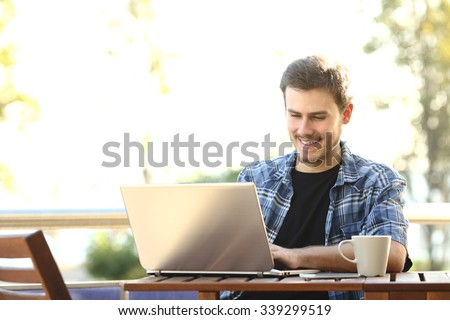 Entrepreneur man working with a laptop in a restaurant terrace or home balcony - stock photo