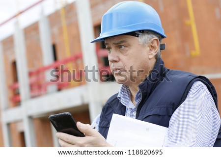 Entrepreneur on construction site using smartphone - stock photo