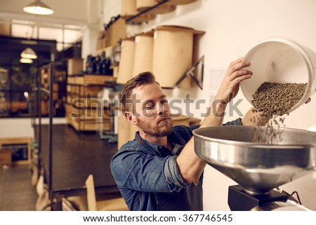 Entrepreneur pouring raw coffee beans into a modern roasting mac - stock photo