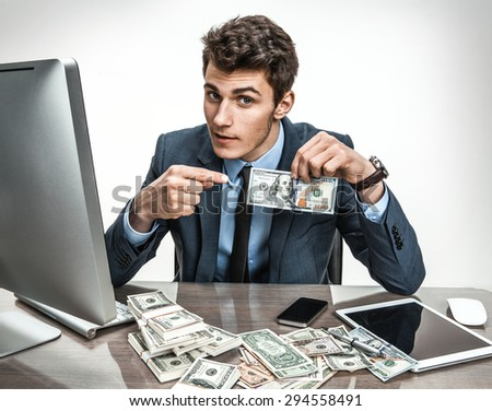 Entrepreneur showing his motivation earnings, profit, income, gain, benefit, margin / modern businessman at his desk with computer and a lot of money - stock photo