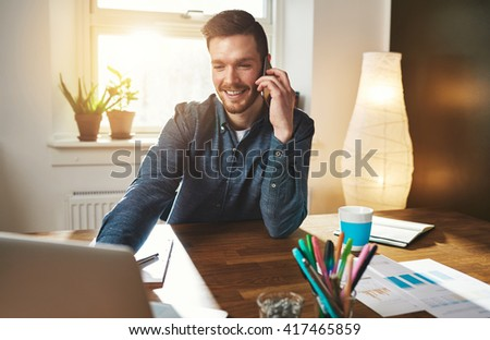 Entrepreneur taking a mobile phone call as he researches information on his laptop computer with a smiles while working from an office at home - stock photo