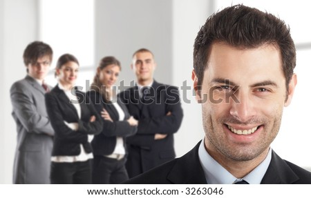 Entrepreneur - with his team behind him in an office environment - people in the background are out of focus - check my gallery for more pictures - stock photo
