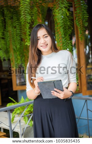 Entrepreneur women use tablet for business plan making in cafe