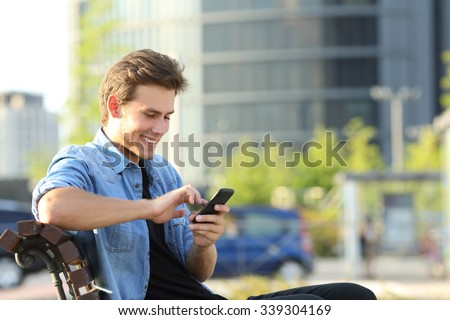 Entrepreneur working texting in a mobile phone sitting on a bench with office buildings in the background - stock photo