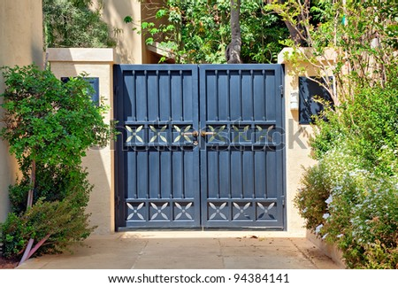Entry black metal gates with gold handles in the garden - stock photo