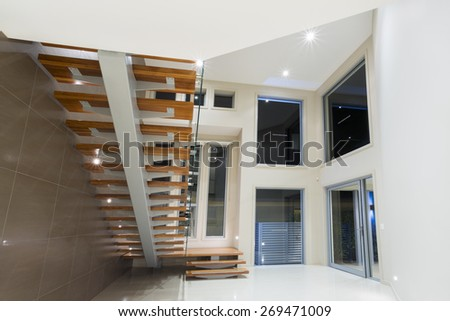 Entry in contemporary mansion with wooden staircase - stock photo