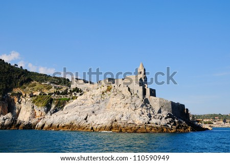 Entry in Portovenere harbour and church san Pietro in Italy in clear calm day - stock photo