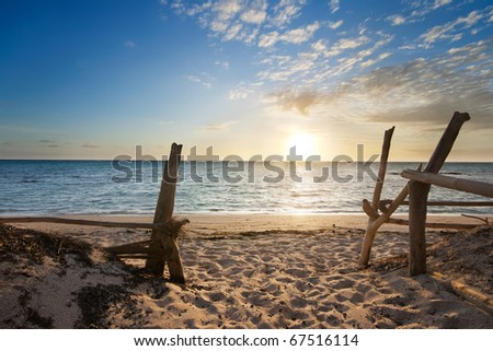 Entry to isolated beach at sunrise with interesting clouds formation - stock photo