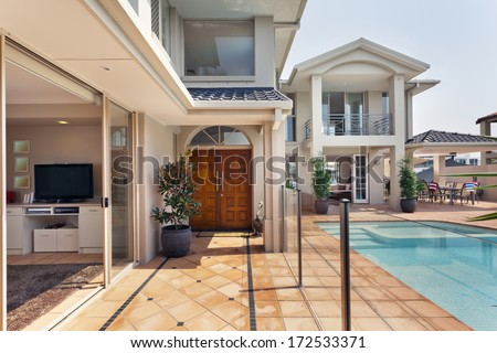 entry way to luxurious australian mansion with pool - stock photo