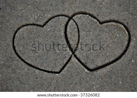 Entwined cookie cutter hearts impression in the sand - stock photo