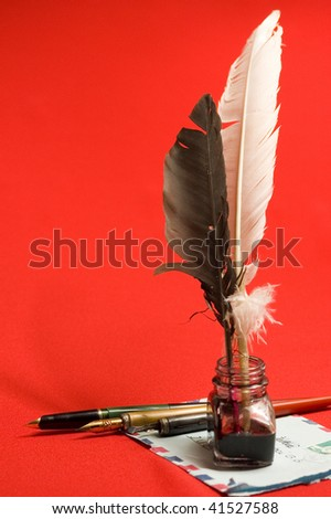 Envelope and feather quill and ink well on red backgrounds - stock photo