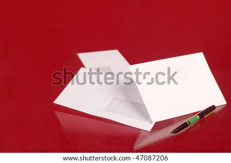Envelope and pen on red backgrounds - stock photo