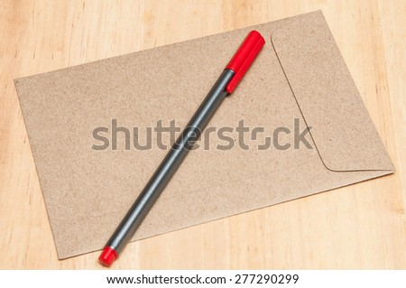 Envelope and red pen on wooden table. - stock photo