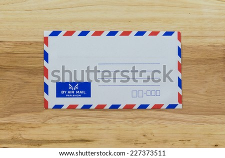 Envelope by air mail isolated on wood