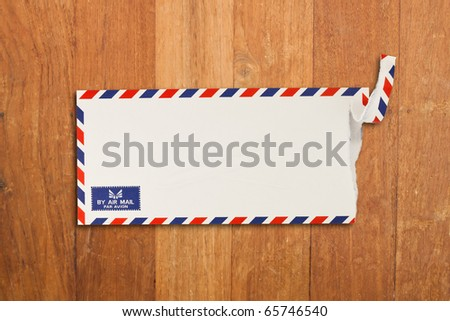 Envelope by air mail isolated on wood - stock photo