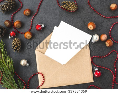Envelope, cones, hazelnuts  and christmas decorations on grey background