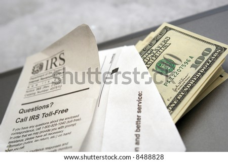 envelope full of money, coming from or going to the IRS - stock photo