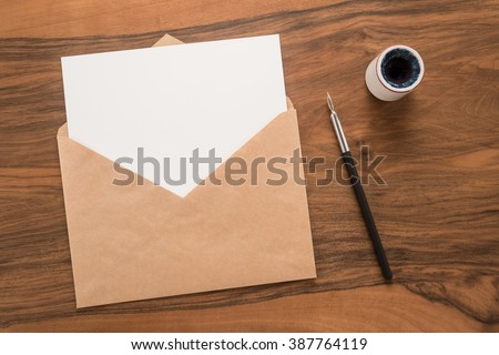 Envelope, ink pen, inkwell on a wooden background   - stock photo