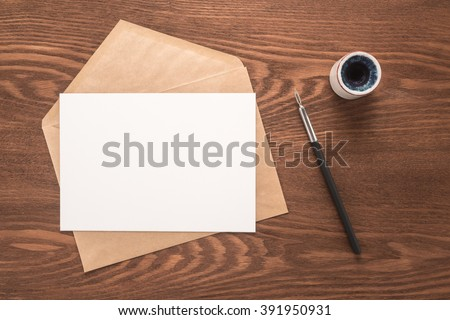 Envelope, ink pen, inkwell on a wooden background