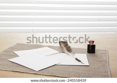 envelope, letter, ink, feather quill pen on the wooden office desk(table) behind white blind. - stock photo