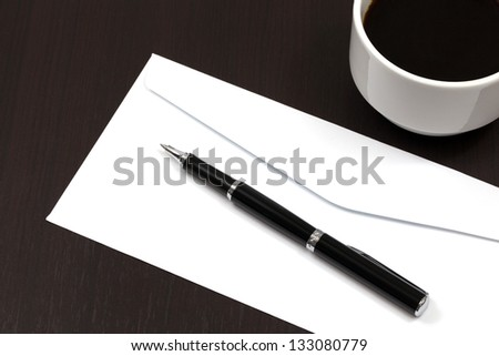 envelope on a table with pen and coffee - stock photo