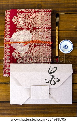 envelope origami flower with hieroglyph with oriental pad near brush for calligraphy - stock photo
