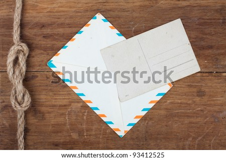 Envelope, postcard and rope on wood background - stock photo