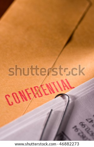 Envelope sealed with confidential stamp with some document on top of it. - stock photo