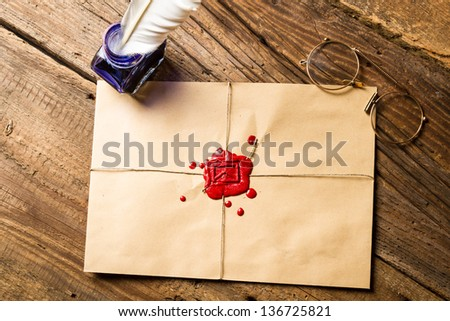 Envelope with imprinted sealing wax and inkwell with blue ink - stock photo